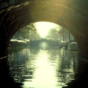 Blick eine Gracht entlang unter einer Brücke hindurch