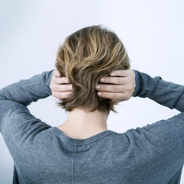 Frau am Arbeitsplatz hält sich die Ohren zu
