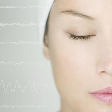 Nahaufname des Kopfes einer Frau, Gehirnwellen im Hintergrund