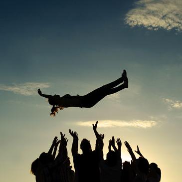 Eine Gruppe Personen wirft eine liegende Person in die Luft
